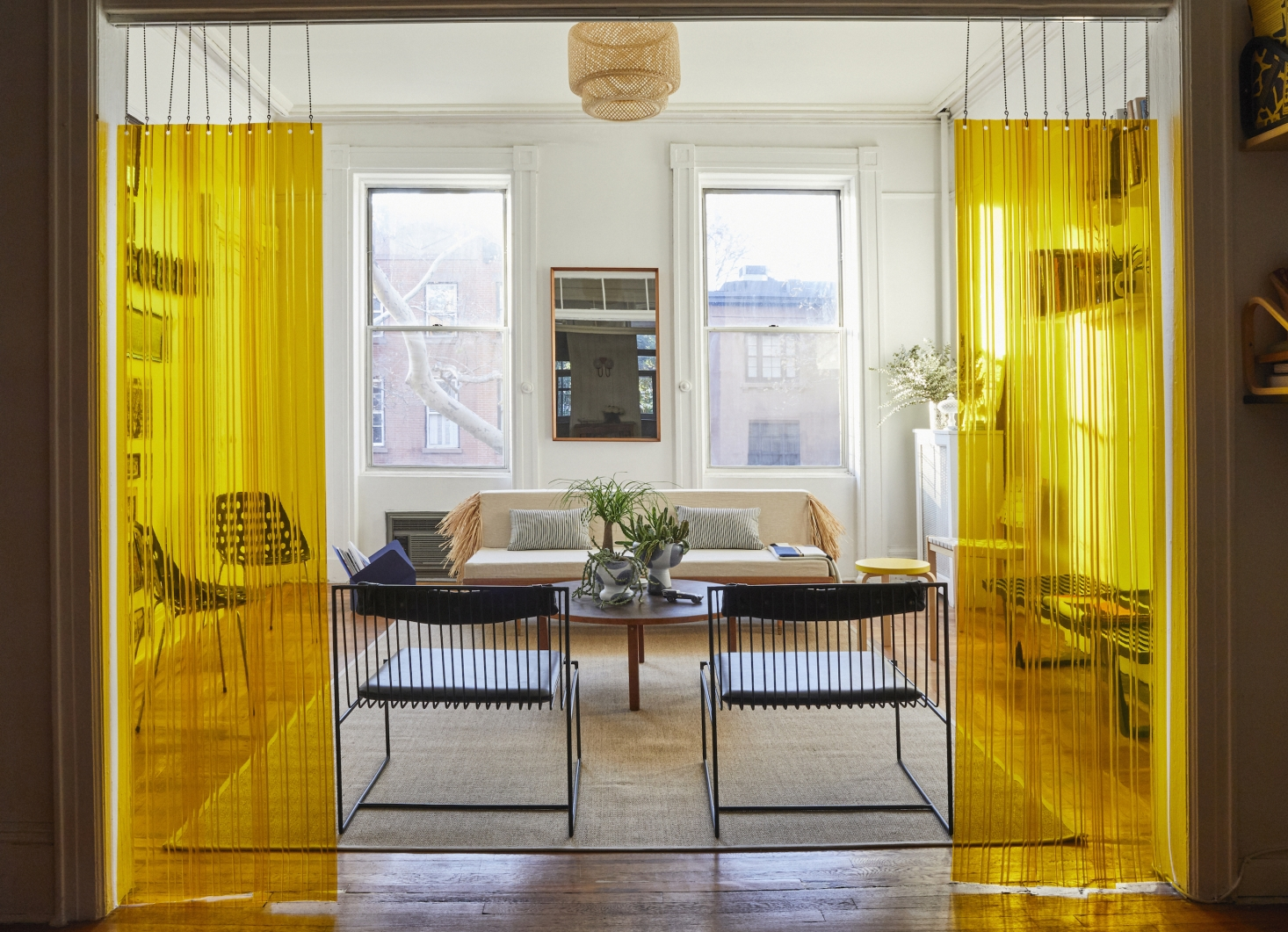 To divide the rooms, Valentin came up with an unconventional solution: yellow strip curtains, the kind typically used in industrial food storage facilities, suspended from a hospital drop chain sourced from a medical supply website. The black metal and leather chairs are Arnold Lounge Chairs from Valentin's company, Bogus Studio ($980 each); the jute Osted Rug is from Ikea. The light fixture is a rental hack—Ikea's Sinnerlig Bamboo Shade—to cover up the landlord's less appealing ceiling fixture.
