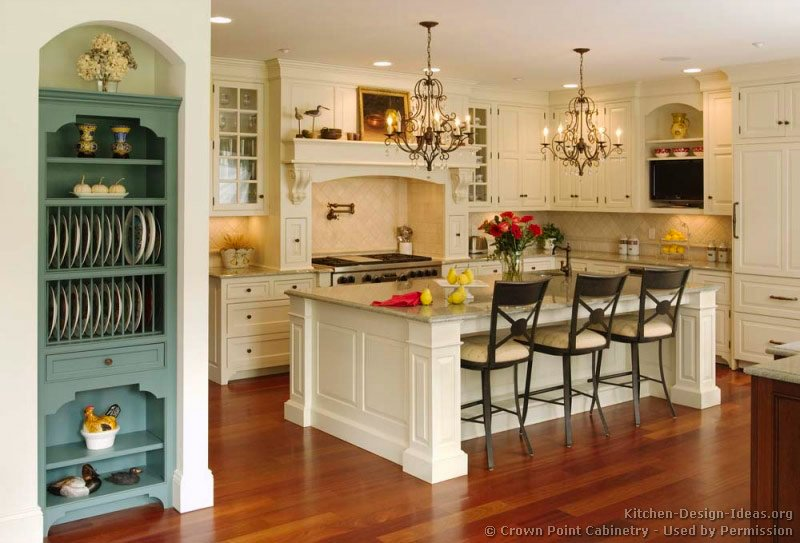A Victorian kitchen with creamy white cabinets, a mantel wood hood, and a large island with chandeliers above
