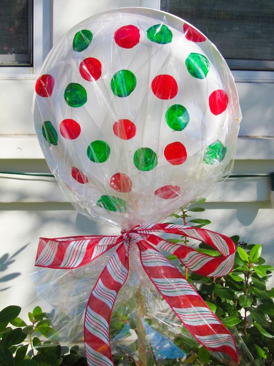 DIY dollar store lollipops for Christmas decor! Use paper plates (glued/stapled together) Christmas colored markers or paint, and cellophane. Stake them into the ground with a stick and tie off with ribbon.