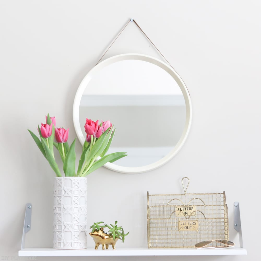 Your entryway can be spruced up with some plants, like these fresh cut tulips and succulent, and a beautiful mirror.