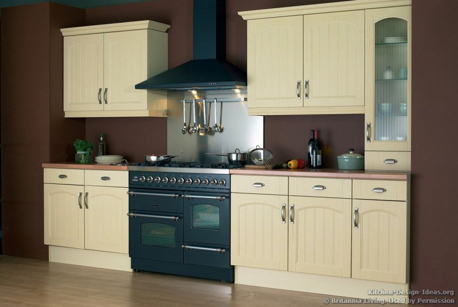 A butter yellow kitchen with a graphite black double oven range