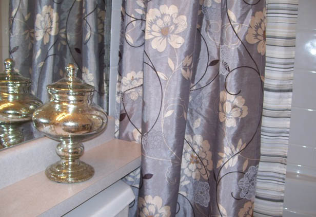 bathroom countertop accessorized with only 1 item with some sheen to it that matches the sheen on the shower curtain